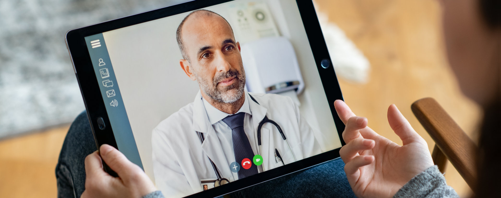 Back view of woman making video call with her doctor while staying at home